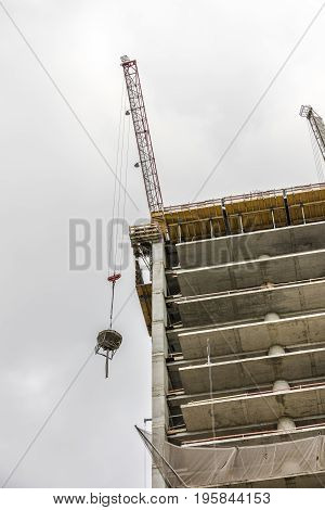 Crane on top of the building under construction lifting concrete bucket