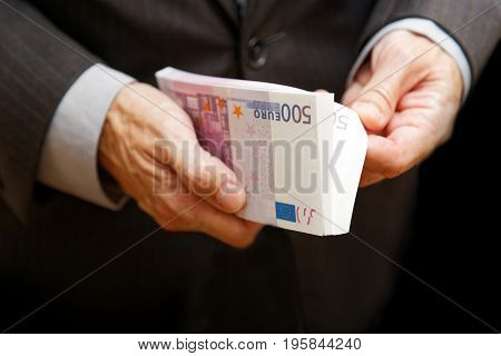 A Man Counts The Money In A Bundle Of Banknotes Of 500 Euros