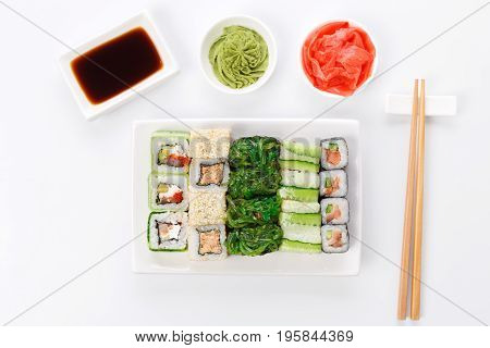 Traditional japanese food restaurant. Top view on sushi set on white plate, soy sauce, ginger, wasabi and chopsticks aside. Colorful rolls and gunkan assortment at white background