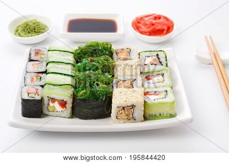Traditional japanese food restaurant. Sushi set on white plate, soy sauce, ginger, wasabi and chopsticks aside. Colorful rolls and gunkan assortment at white background, pov