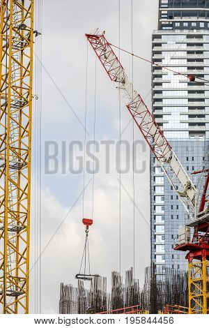 Tower construction crane moves parts on construction site with corporate building on background and second crane vertical
