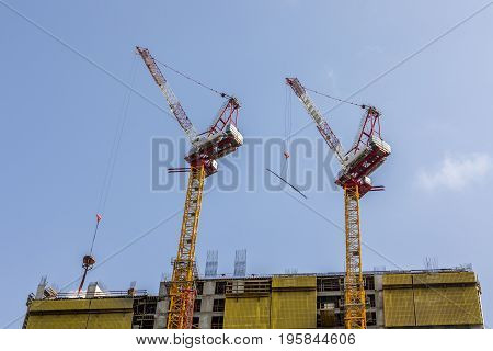 Two building construction tower cranes move load on top of a building with yellow panels blue sky