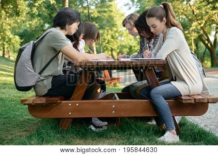Image of multiethnic group of concentrated young people sitting and studying outdoors. Looking aside.