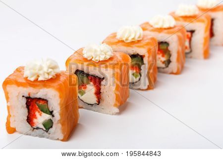 Sushi japanese restaurant delivery. Set of salmon and avocado rolls with decoration of philadelphia cheese closeup at white, pov. Healthy food background with copy space