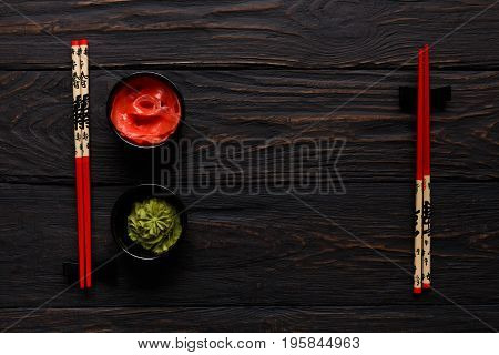 Pieces of traditional japanese tablewear. Red chopsticks with Bon appetite written in hierogliphs, small bowls with ginger and wasabi on dark wooden table. Top view, flat lay, copy space, background