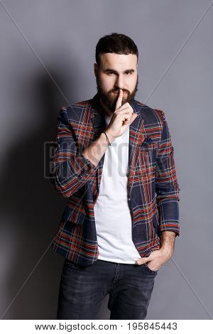 Bearded man shows hush be quiet. Handsome hipster holding finger at his lips, gray studio background, copy space. Secret, privacy concept