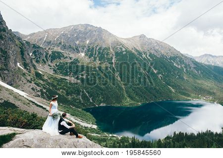 bride with the beautiful blue dress and groom with views of the beautiful green mountains and lake with blue water