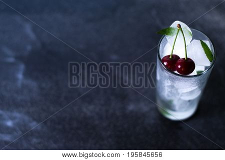 Natural ice in a glass with cherries on a black background with copy space.
