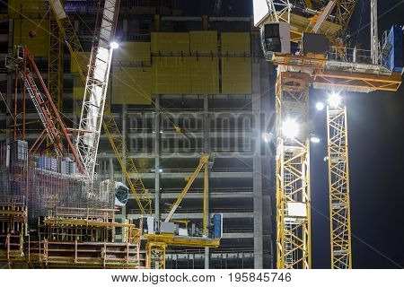 Construction building site with three tower cranes building under construction lighted with projectors at night