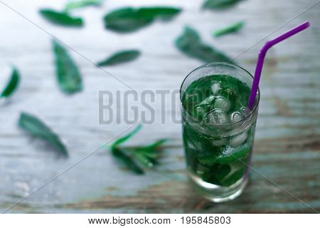 Glass with ice and mint leaves on a blue background