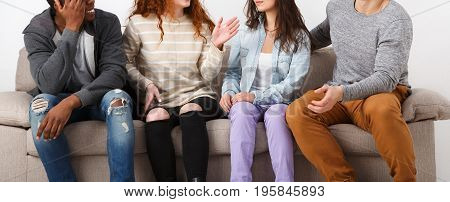 Young multiethnic couples friends crop, casual people having fun, sitting on couch indoors and laughing
