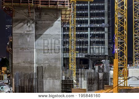 Construction building site with three tower crane masts building under construction lighted with projectors at night