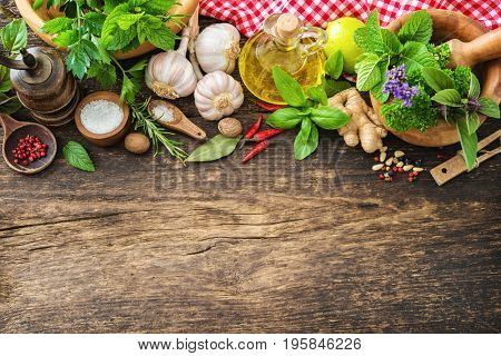 Fresh herbs and spices on wooden table. Top view with copy space