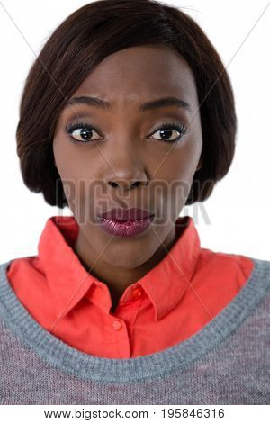 Portrait of young woman puckering against white background
