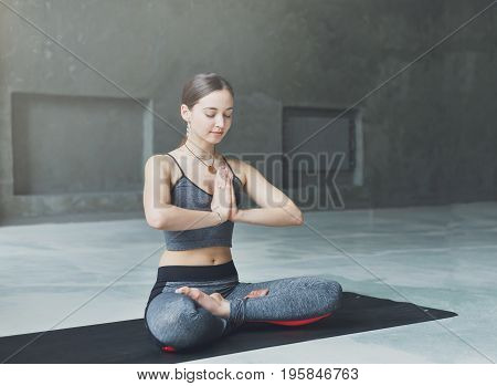 Attractive girl practicing yoga sitting in padmasana. Young woman in lotus pose, namaste with closed eyes on mat at sport club interior, copy space