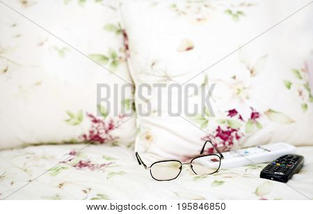 TV remote controls and eye wear left on the sofa indoor cropped photo