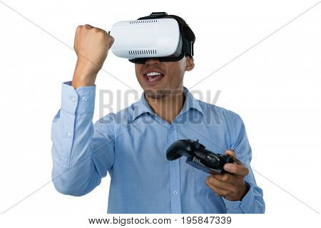 Happy businessman with vr glasses clenching fist while playing video game against white background