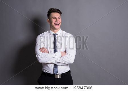 Successful businessman. Confident young man standing and smiling at gray studio background
