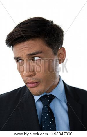 Close up of young businessman looking away against white background