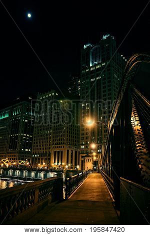 Dark city steel bridge and river promenade at night in Chicago. Surreal urban scene with the moon over skyscrapers.