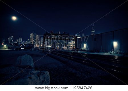 Chicago skyline at night with train tracks leading into the city.