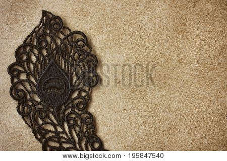 Detail of black lace on old texture paper closeup space for text vintage composition