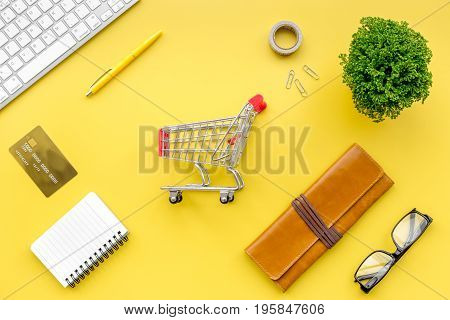 Online shopping. Bank card in purse nearby keyboard and mini shopping cart on yellow background top view.
