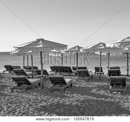 sea beach landscape with sunbeds and sunshades of monochrome tone
