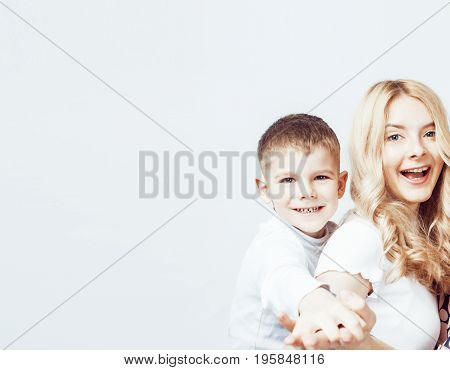 young modern blond curly mother with cute son together happy smiling family posing cheerful on white background, lifestyle people concept, sister and brother friends close up