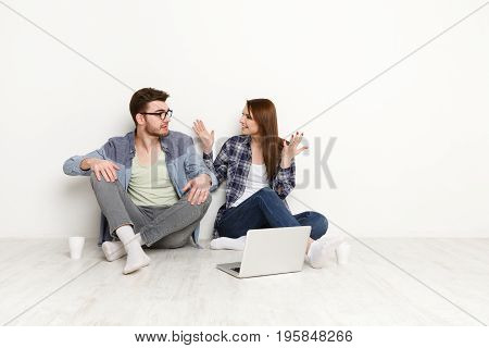 Couple in casual with laptop. Woman sharing news with unpleasantly surprised man in new apartment, sitting at empty living room at home