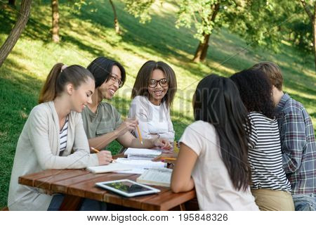 Image of multiethnic group of young students sitting and studying outdoors while talking. Looking aside.