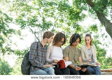 Picture of multiethnic group of concentrated young students sitting studying outdoors. Looking aside.