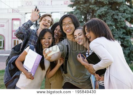 Picture of multiethnic group of young happy students standing outdoors make selfie by phone. Looking aside.