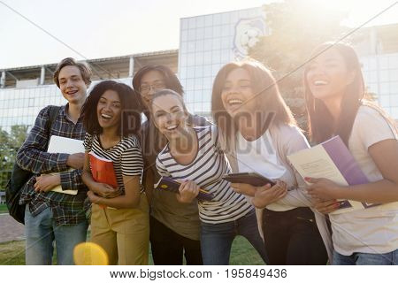 Photo of multiethnic group of young cheerful students standing outdoors. Looking at camera.