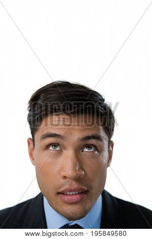 Close up of businessman looking up against white background