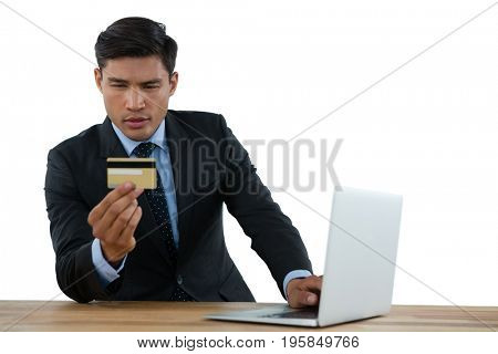 Businessman holding credit card while using laptop at table against white background