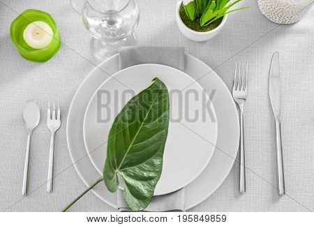 Beautiful table setting with green tropical leaf