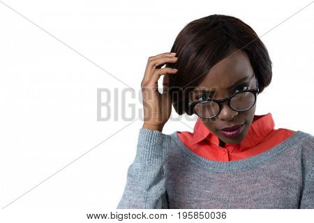 Confused woman with hand in hair against white background