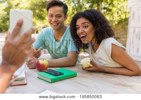 Picture of surprised young multiethnic friends students talking with each other outdoors looking at the display of mobile phone.