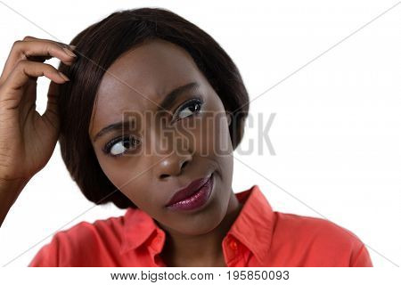 Close up of confused young woman against white background