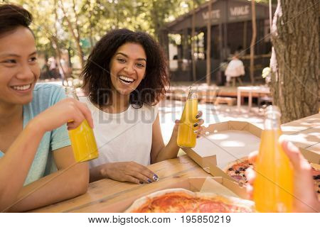 Picture of happy young multiethnic friends students outdoors drinking juice eating pizza and talking with each other. African lady looking camera.