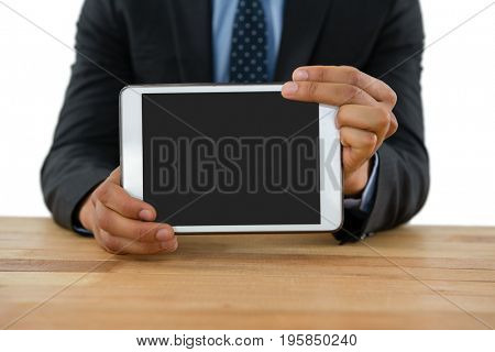 Mid section of businessman showing tablet while sitting at table against white background