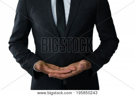 Mid section of businessman doing hand gesture while standing against white background