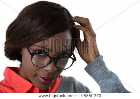 Close up of confused young woman wearing eyeglasses against white background