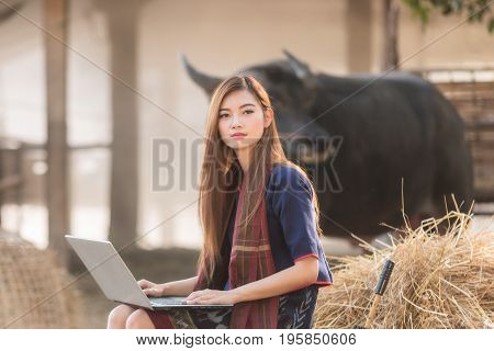 Beautiful Woman are using laptop computer in the rice fieldWoman wear Thai traditional costume.