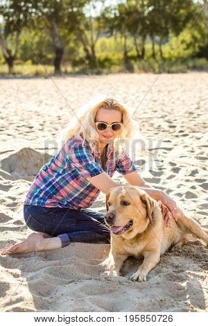Portrait of young beautiful woman in sunglasses sitting on sand beach with golden retriever dog. Girl with dog by sea. Happiness and friendship. Pet and woman. Woman playing with dog on sea shore