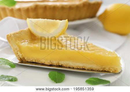 Piece of lemon pie with mints leaves on plate
