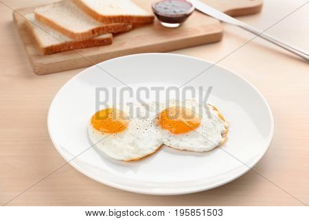 Composition with sunny side up fried eggs, bread and jam on wooden table