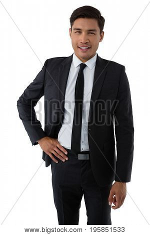 Portrait of smiling young businessman with hand on hip standing against white background