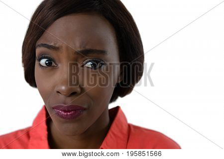 Close up of confused woman making face against white background